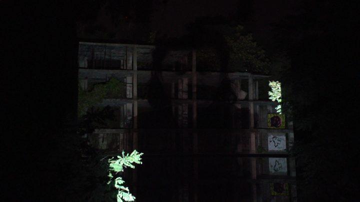 Le operaie della Viscosa di Roma—omaggio a un Monumento Naturale (per una scena di Porta Maggiore): Proiezione notturna estranea n. 6; Sulla struttura di cemento (mostro) nel Lago Bullicante Ex Snia, Rome, Italy, 2020, public projection. Video frame. © mgf